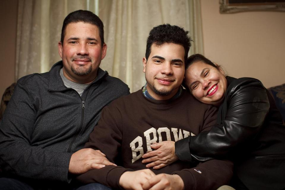 "03/17/2015 - Providence, RI - Alejandro Claudio, cq, and his parents, Alejandro Claudio, cq, left, and Maribel Claudio, cq, right. Alejandro is now a freshman at Brown University and gained a full-ride scholarship to the Ivy League school, which is the only way that the son of poor immigrant parents could hope to attend. He is shocked regularly by the huge contrast between his world at school and the world he's used to at home. Claudio is majoring in economics. ÒIf I fail, IÕm going back to poverty, to working in a factory,"" said Claudio. ""I need to get good grades and get a job that pays well enough to help feed my family,Ó added Claudio. Topic: 041215ivyleague. Photo by Dina Rudick/Globe Staff."