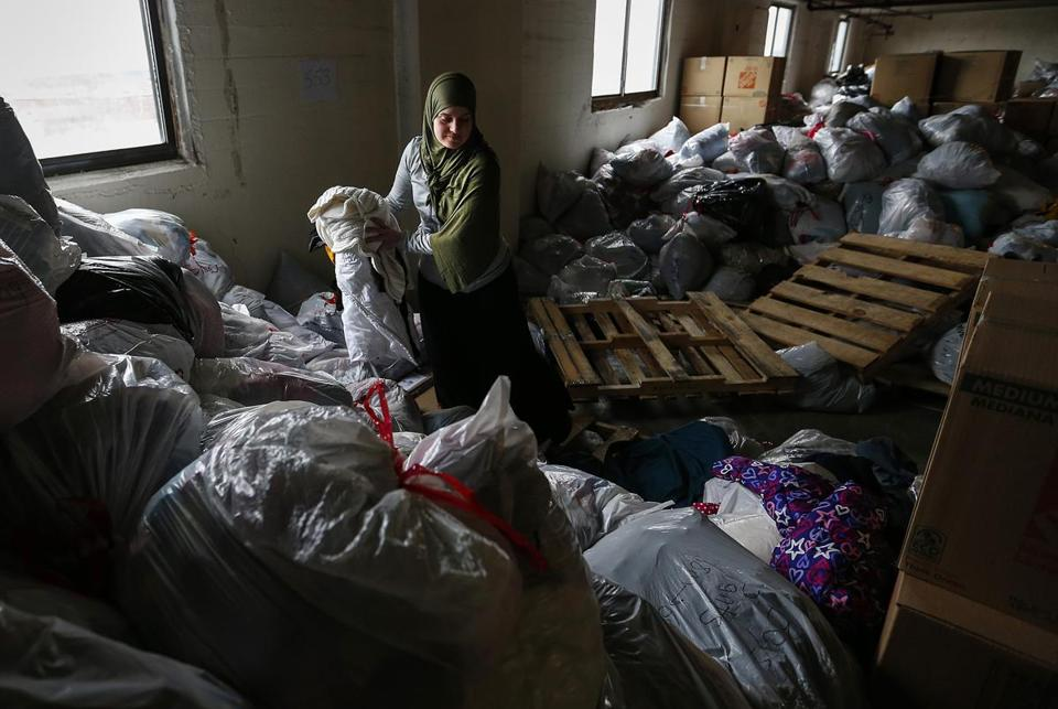 Nadia Alawa sorted donated clothing to be bagged and shipped at a Nashua storage facility.
