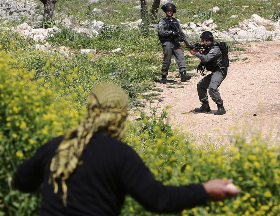 A Palestinian protester took position to throw stones toward Israeli security forces in the occupied West Bank on March 13.