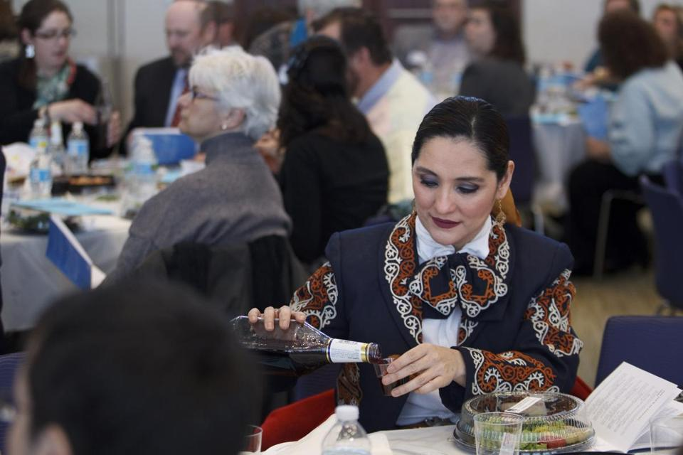 "Veronica Robles of Boston poured a small cup of wine during the eighth annual ""A Nation of Immigrants"" Community Seder, held on Sunday at the UMass Boston campus."