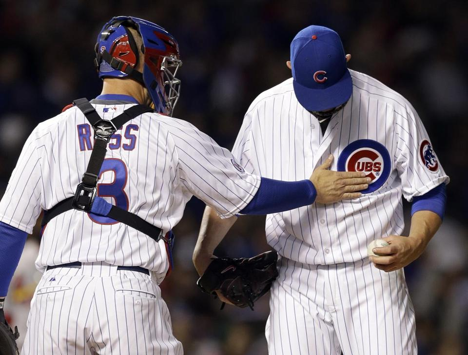 Former Red Sox David Ross (left) and Jon Lester meet on the mound during the Cubs' opener on Sunday night. (AP Photo/Nam Y. Huh)