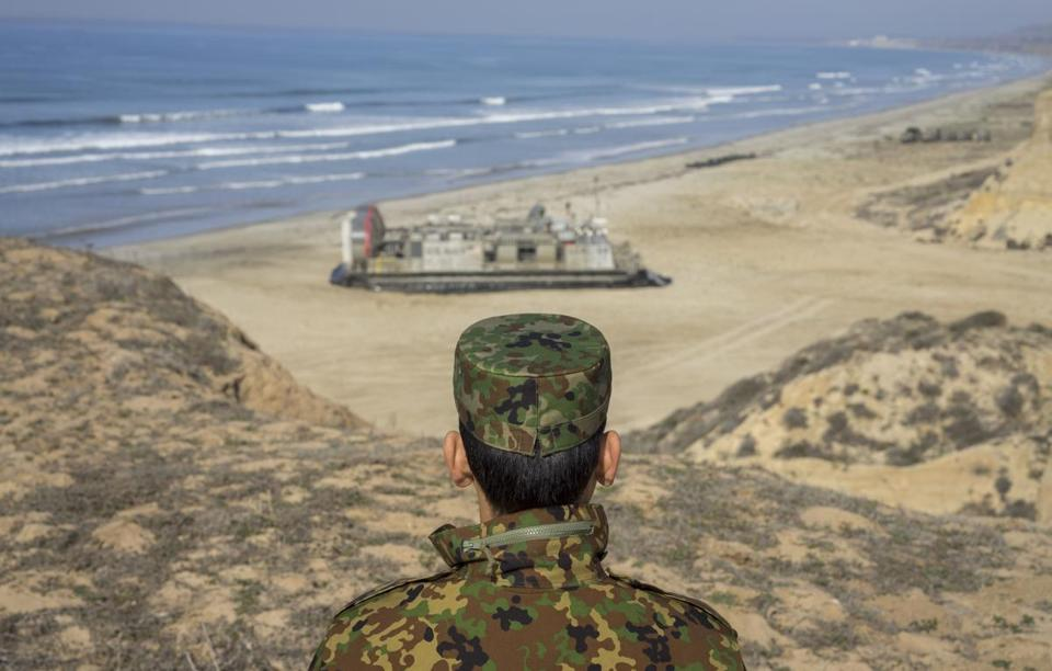 A Japanese officer watches as a Landing Craft Air Cushion transports US Marines and sailors and soldiers from Japan during a joint military exercise in California in 2014.