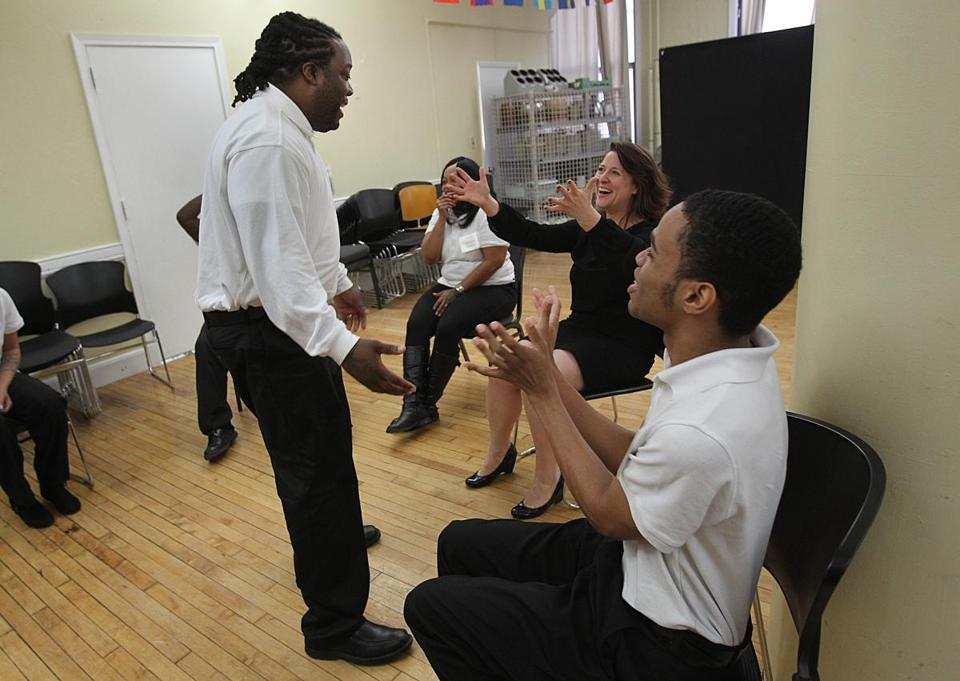 Student Cornelius Sanders (left) won cheers from teacher Christy Betit and student Joseph Singletary during a Mel King Initiative class.