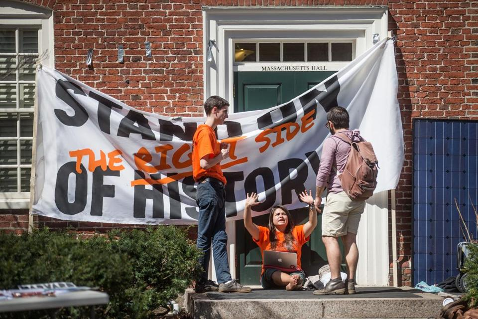 Tyler Van Valkenburg (left) and Maryssa Baron (center), of Divest Harvard, spoke to a fellow student while blocking the entrance to a Harvard administration building.