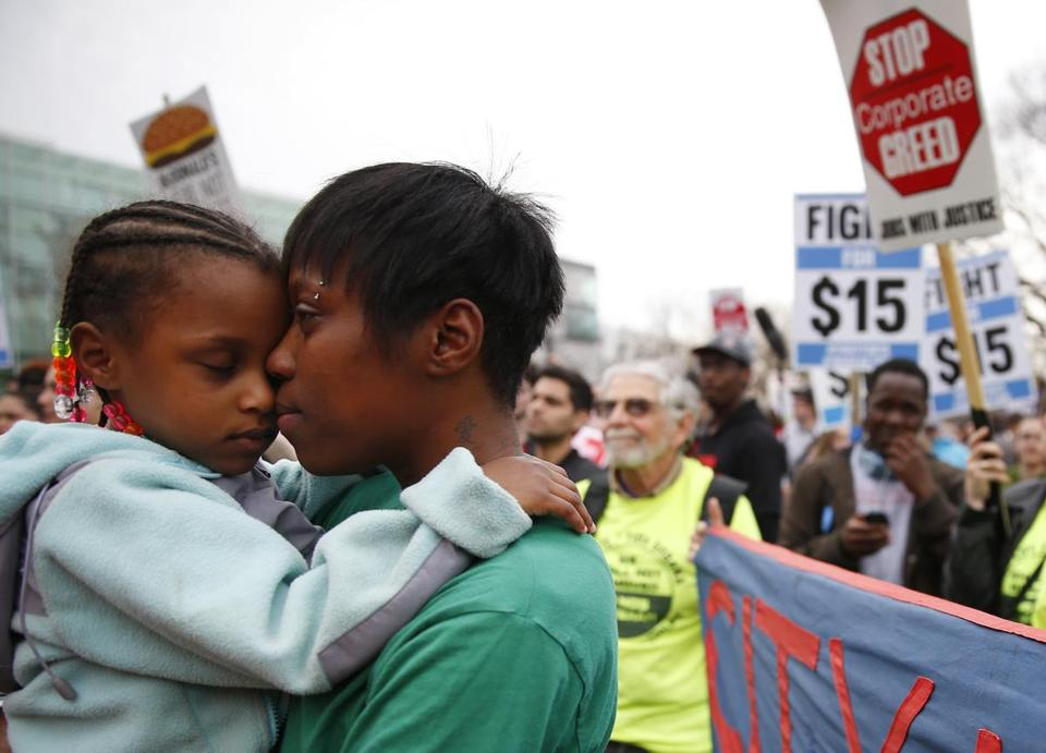 Latrese Williams, of Dedham, held her daughter, Desirae Shealey, 4, at Tuesday's rally.