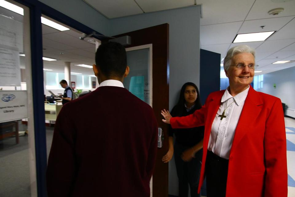 Sister Mary Murphy, the founding president of Notre Dame school, holds the door for students.