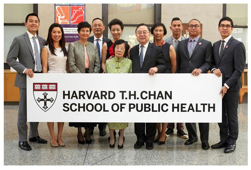 The Chan family at the dedication ceremony for Harvard's public health school in September 2014. Chan's brother (and business partner) Ronnie stands at center with his arm around their mother (in green); Gerald Chan is fourth from the left.