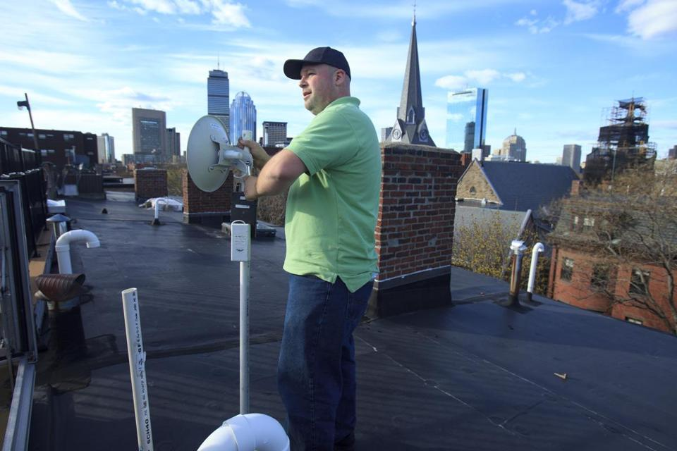"4/28/2015 - Boston, MA - Max Ariza is the field operations manager at netBlazr, which offers clients a ""WISP"" (Wireless Internet Service Provider.) It's basic Internet service without the cable -- super-fast and right to your door. Ariza installed service on a South End roof on Tuesday, April 28, 2015. He site-checks by going up on people's roofs to make sure they can see another of the company's boxes on another rooftop (the service only works line-of-sight) and works with a team to install the ""radio"" boxes and then strings wiring to the customer's computer. Topic: onthejob. Story by Robert Gavin/Globe Staff. Photo by Dina Rudick/Globe Staff."