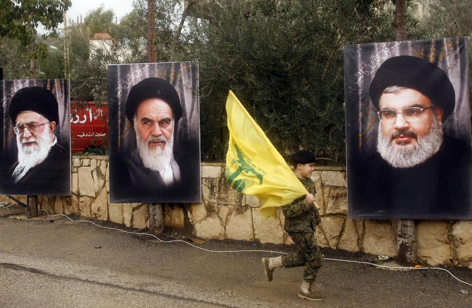 A Lebanese boy with a Hezbollah flag ran past portraits of Iran's Supreme Leader Ayatollah Ali Khamenei (left); the founder of Iran's Islamic Republic, the late Ayatollah Ruhollah Khomeini (center); and Hezbollah leader Hassan Nasrallah in the southern Lebanese town of Jibsheet in February.