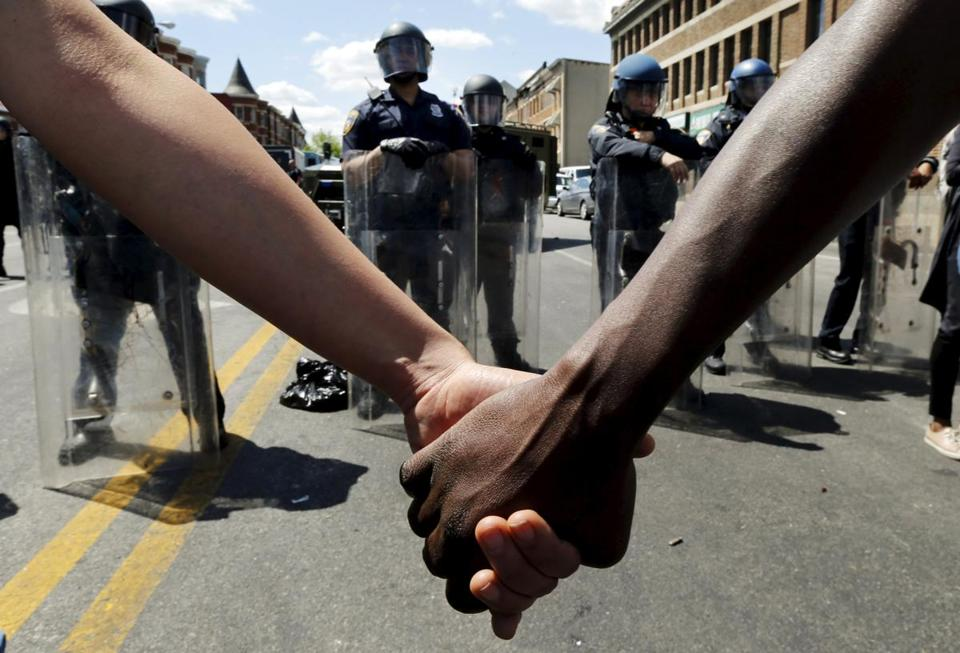 Members of the community held hands in front of police officers in riot gear outside a recently looted and burned CVS store in Baltimore.
