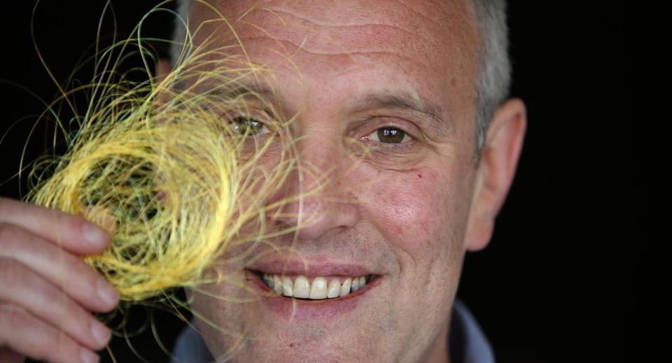 Yoel Fink holds a bundle of yellow fibers.