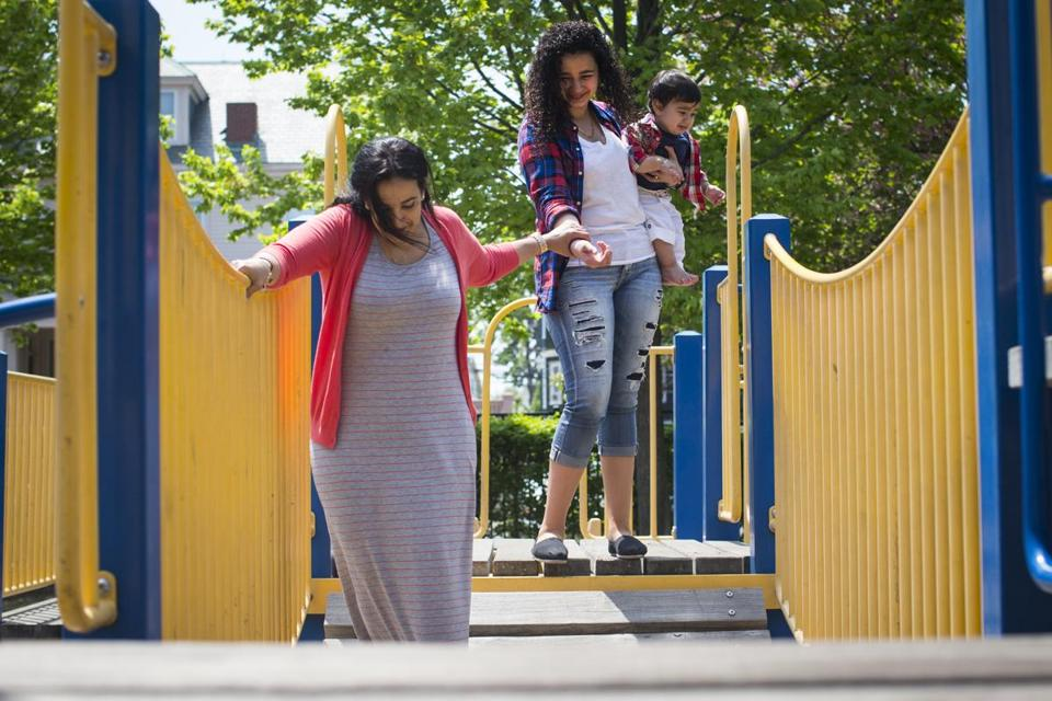 Sarah Khamis (holding her brother Karar Kareem) and her mother Zohra Khamis at a playground in Revere.
