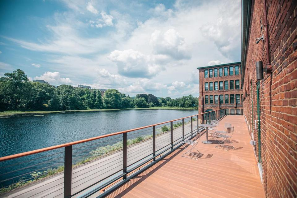 "Employees at CloudLock, a cloud security company based in the Watch Factory building in Waltham, enjoy dedicated deck space on the river. Suburban towns are branding the area ""Charles River Mill District."""