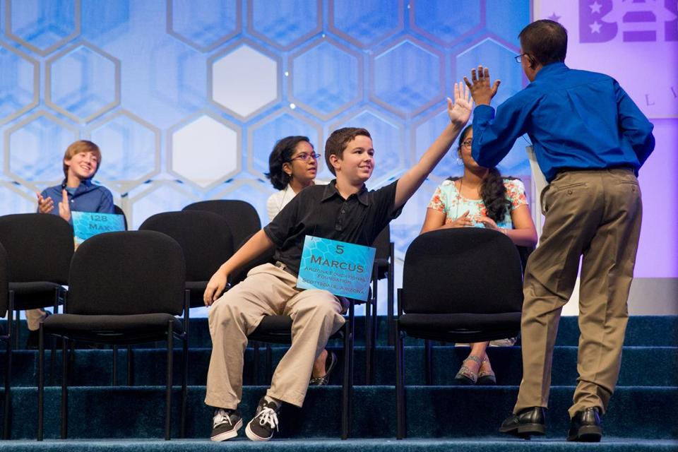 "Marcus Behling, 13, of Scottsdale, Ariz. (center) high-fived Dev Jaiswal, 13, of Jackson, Miss., after he correctly spelled ""naranjilla."""