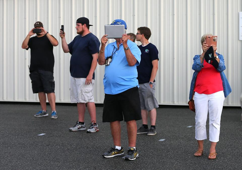Family members and workers took photos on the ground at Lawrence Regional Airport in North Andover.