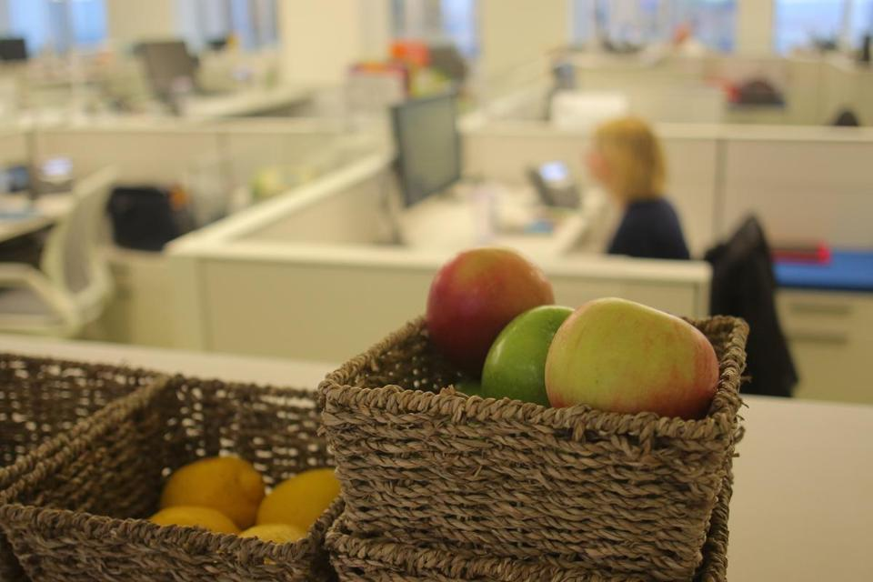 Fresh fruit is available in a walkway near employee cubicles.