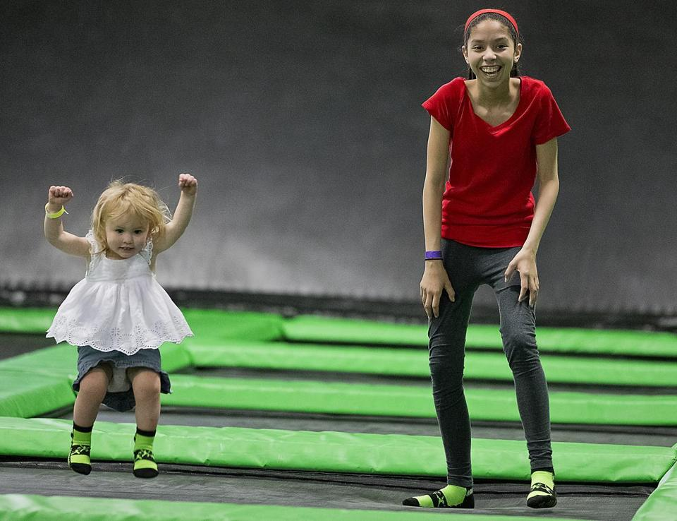 Audrey Cusano, 2, and Briana Guzman, 12, jumped on a trampoline in Watertown.
