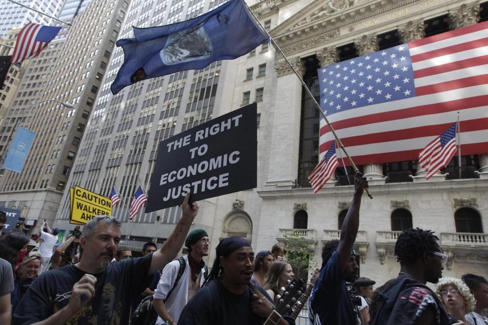 Occupy Wall Street protesters walked past the New York Stock Exchange.