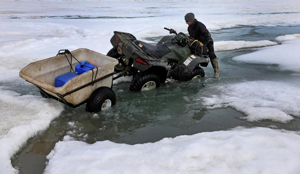 Josh Jones worked to get his ATV out of water on the ice near Barrow, Alaska.