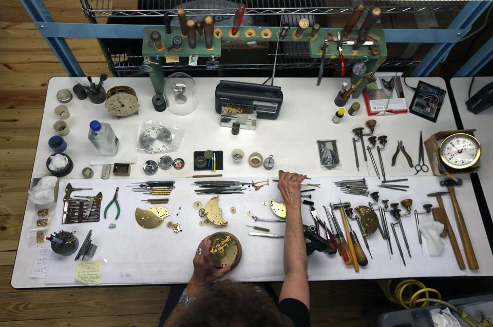 Longtime Chelsea Clock employee Jean Yeo, a master clockmaker works, on clock mechanisms.
