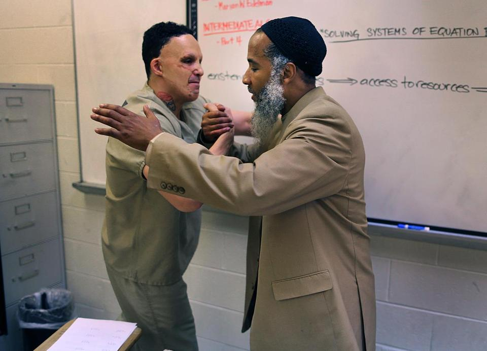 Inmate Joseph Smith (left) embraces Ismail Abdurrashid after class at South Bay House of Correction.