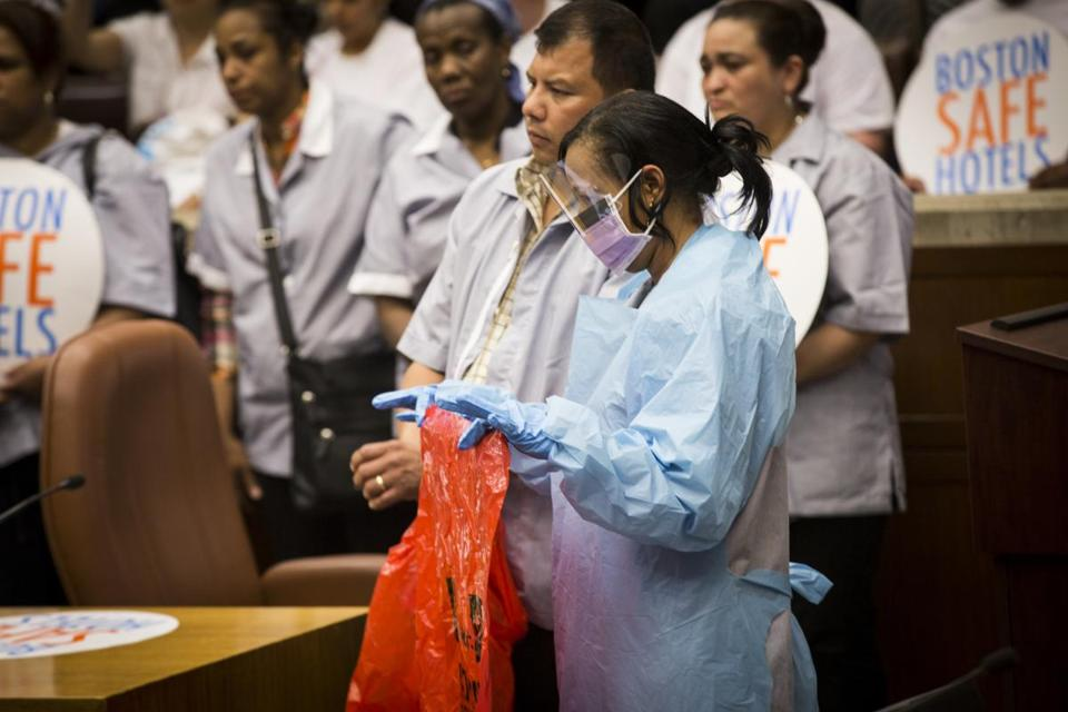 Boston, Massachusetts - 6/25/2015 - Wyndham Hotel house keeper Freddie Delorbe demonstrates the type of protection that should be used to clean what workers at the hotel consider hazardous working conditions at the Wyndham during a city council hearing at City Hall in Boston, Massachusetts, June 25, 2015. Workers claim sick people going for treatment at Massachusetts General are staying in the hotel and are not disposing of hazardous needles and other materials properly and that they don't have the facilities to do it. (Keith Bedford/Globe Staff)