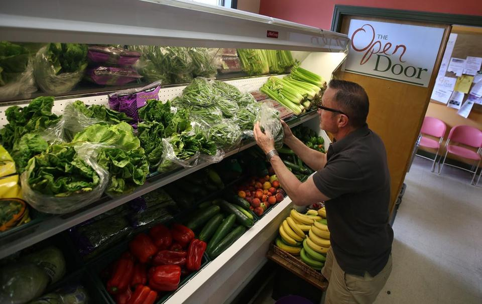 Kevin Brisson, food pantry manager at Gloucester's Open Door, stocked fresh produce. The pantry is among many in the state that are remodeling facilities to offer more fresh produce, fruits, and meats to clients.