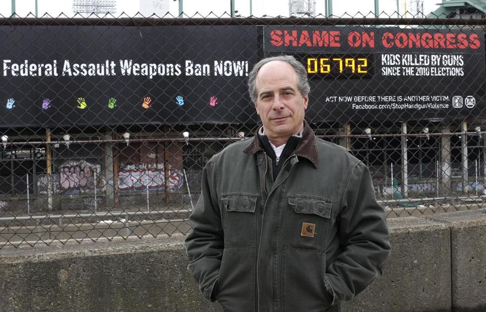 John Rosenthal shown before his old billboard along the Massachusetts Turnpike.