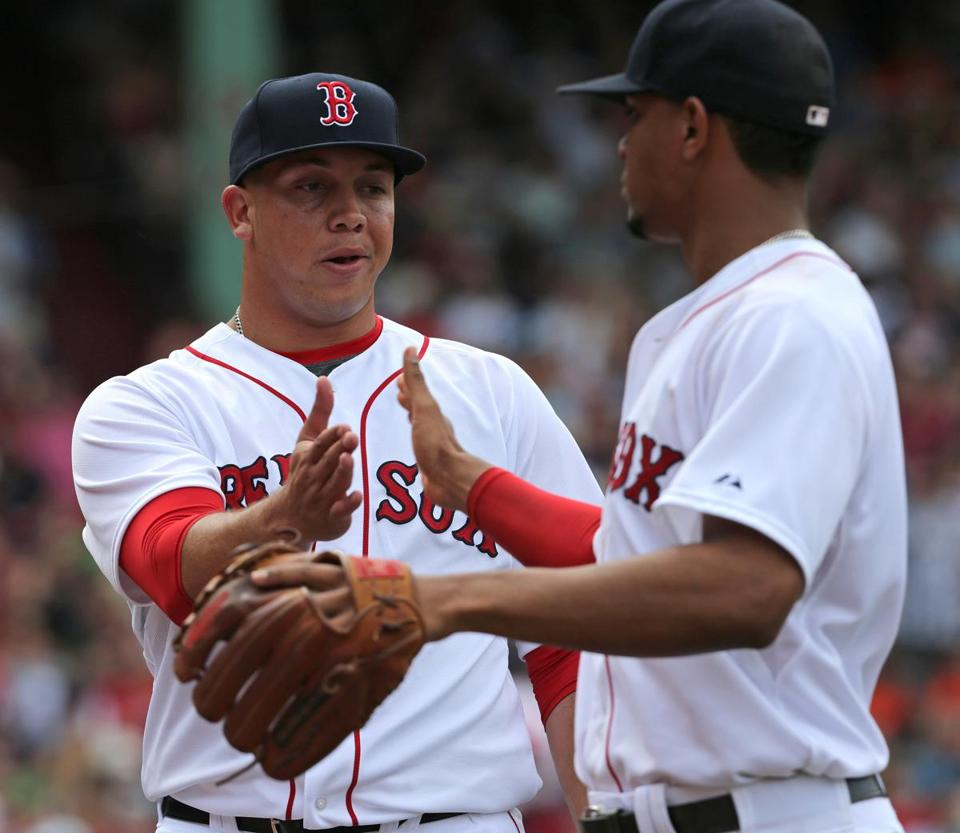 Boston, MA - 06/25/15 - (6th inning) Boston Red Sox relief pitcher Jonathan Aro (65) slaps hands with Boston Red Sox shortstop Xander Bogaerts (2) after getting the third out in the sixth inning. The Boston Red Sox take on the Baltimore Orioles in Game 3 of a three game series at Fenway Park. - (Barry Chin/Globe Staff), Section: Sports, Reporter: Julian Benbow, Topic: 26Red Sox-Orioles, LOID: 8.1.1611224443.