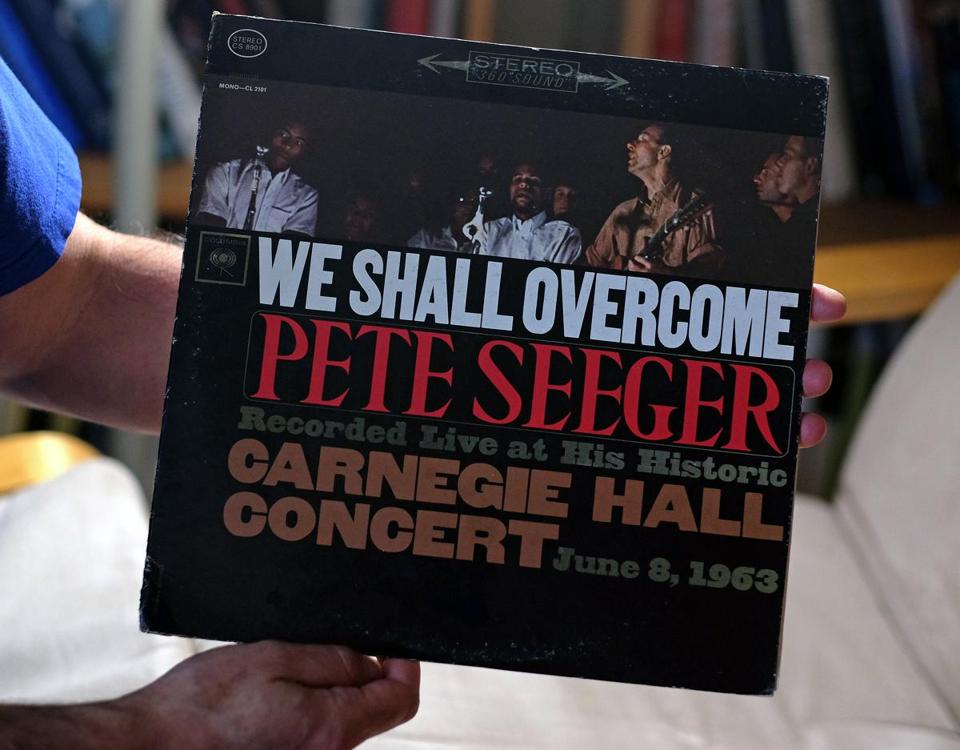 Michael Lowenthal holds a Peter Seeger album, his favorite growing up.