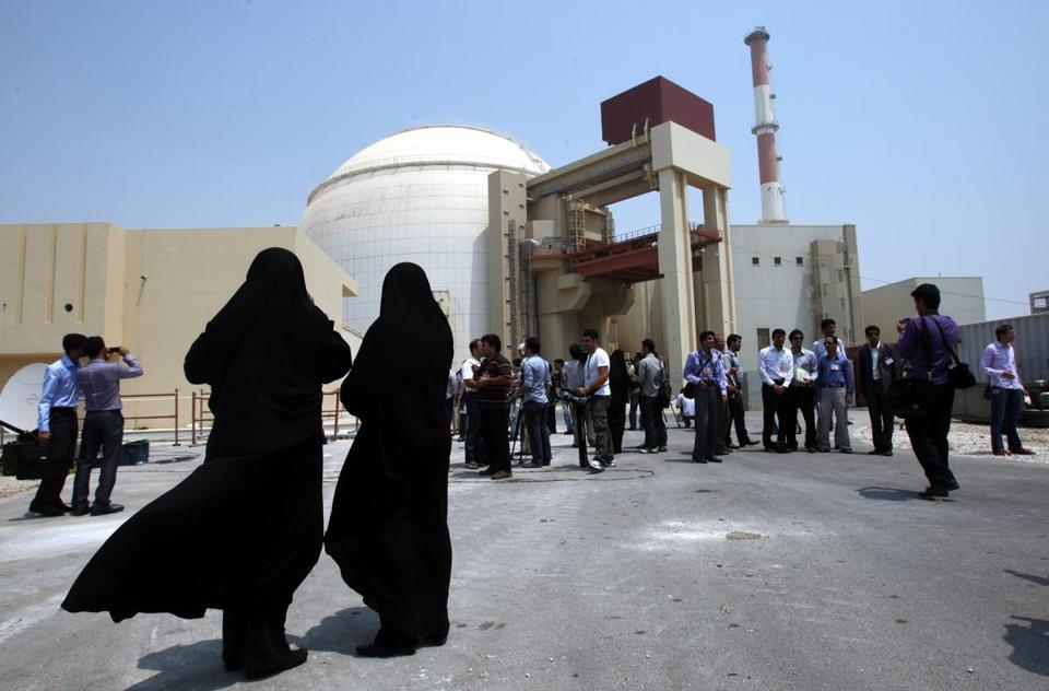 Iranian security officials looked at members of the media in front of the Bushehr nuclear plant.