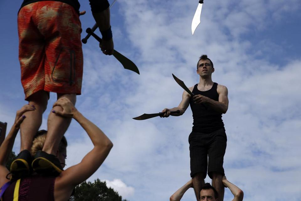 Kira Lapaire of Northhampton (bottom left) held her husband, Rocco, on her shoulders as he juggled knives with Tim Ellis of Brighton (top right) while he stood on the shoulders of Benjamin Reynolds of Somerville as they practiced for the opening.