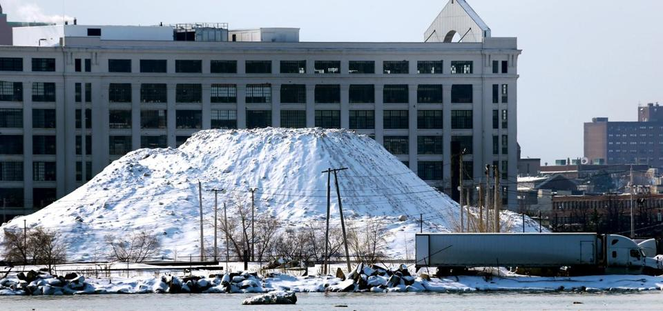 BOSTON, MA : Boston's massive snow pile has officially melted here seen at the Seaport District..A view of the pile on 2/19/2015:The ever growning snowfarm seen from Boston Harbor gets to be climbing slowly to the height of 666 Summer Street. (David L Ryan/Globe Staff Photo) SECTION: METRO TOPIC 15snowpilepic