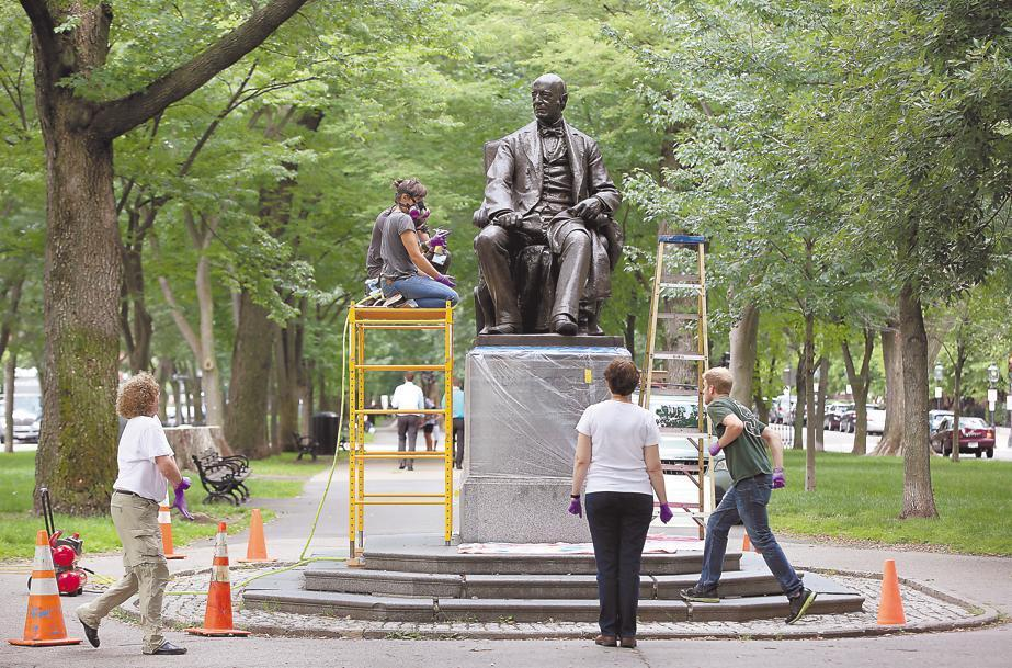 Rika Smith McNally (front) and her crew work on the William Lloyd Garrison statue on the Commonwealth Avenue Mall.