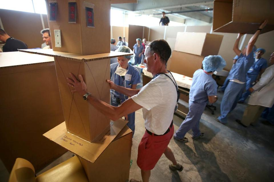 "Clinicians reposition sections of the ""cardboard city"" to find the optimum operating room layout during a mock exercise."