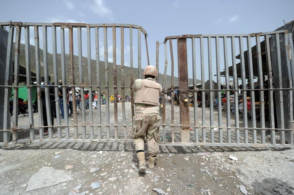 A Dominican soldier watched the border crossing at Malpasse, Haiti, in June.