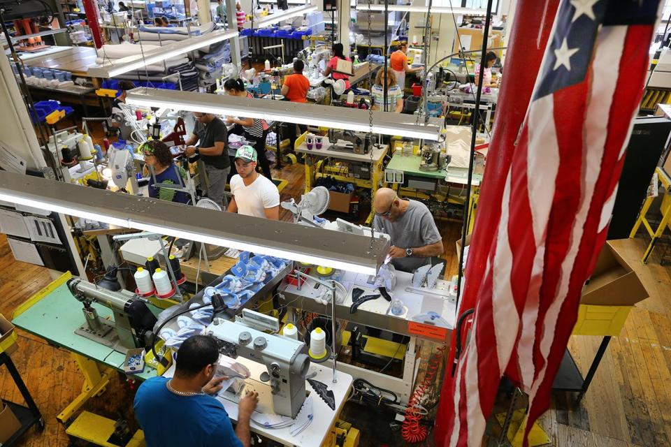 The New Balance manufacturing factory in Lawrence. An American flag hangs in an aisle above a sewing area. Boston Globe staff photo by John Tlumacki