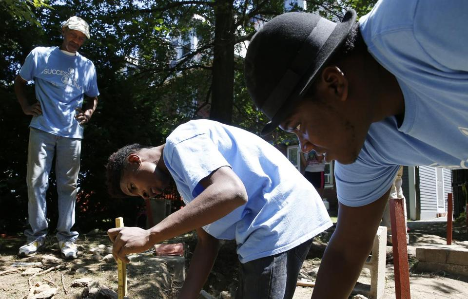 Kevin Corbin, city of Boston supervisor of the Industrial School for Girls site, watched as Khaivon Castro, 21, of the South End measured the depth of a hole dug to excavate part of a foundation while Jalen Campbell, 19, of Mattapan helped hold a line level.