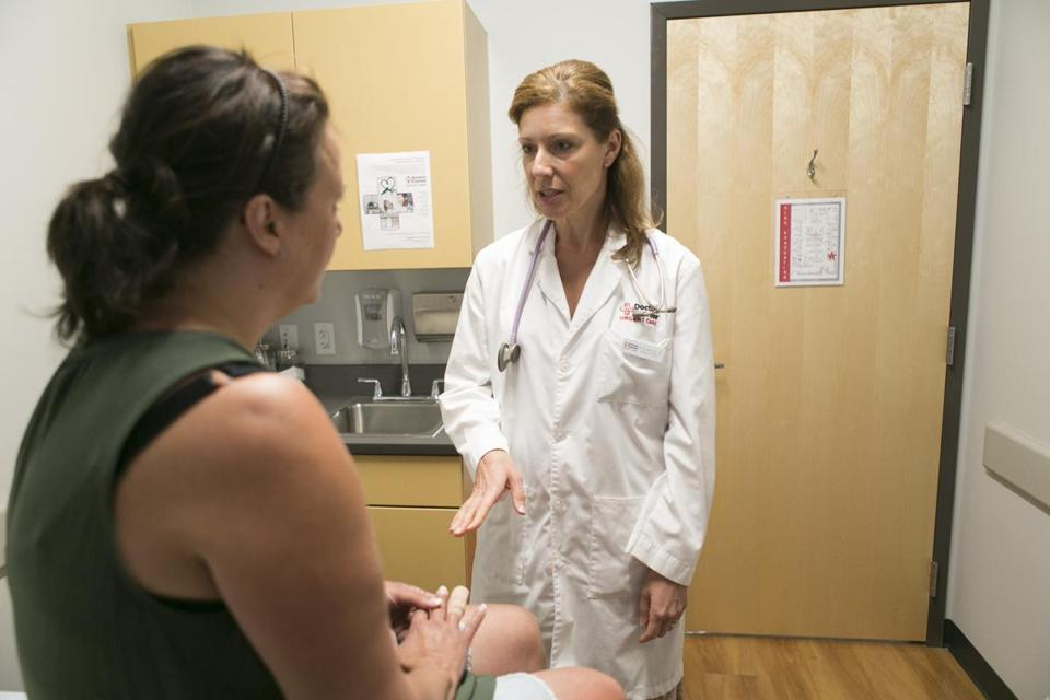 At AFC Doctors Express, in Burlington, Dr. Kristina Orio consulted with a patient who was following up on a hand injury. Credit: Katherine Taylor for The Boston Globe