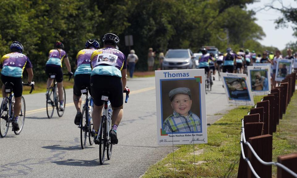 Riders passed by signs of children helped by the Jimmy Fund as they participate in the Pan-Mass Challenge in Lakeville on Saturday.
