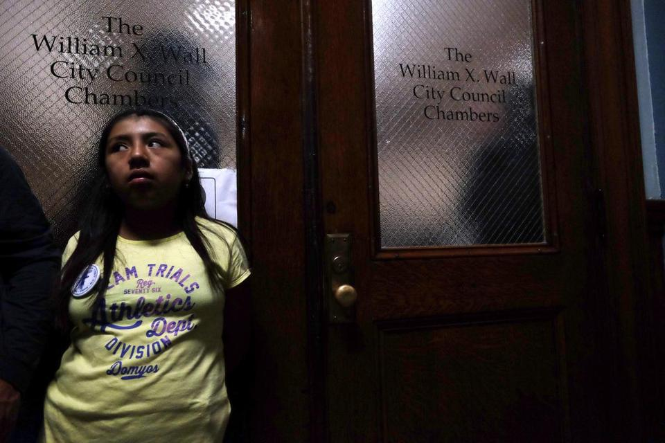 A young girl who was part of the overflow crowd waited outside the City Council chambers during Tuesday night's vote.