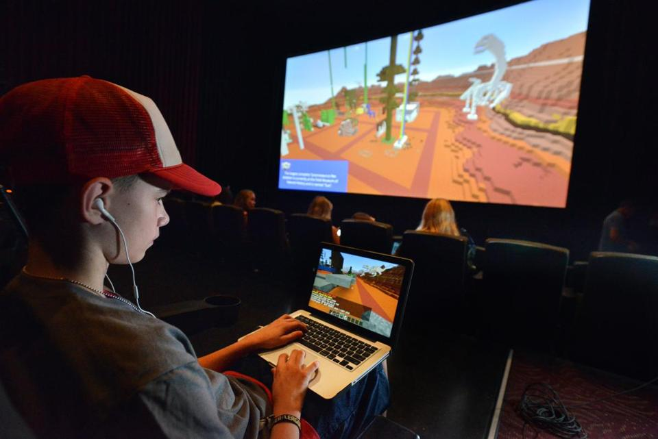 Gavin Chambers, 15, of Windham, Maine, plays on his laptop while the theater screen showed another view of the action during the Super League Gaming Minecraft tournament.