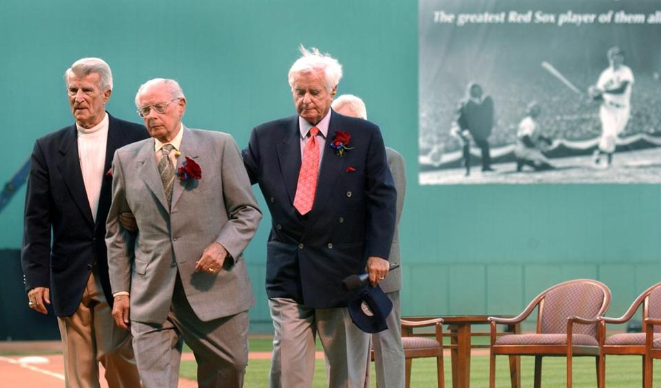 "REMOTE TRANSMISSION--- 7-22-2002:Boston,MA:GLOBE STAFF PHOTO/JIM DAVIS................After their ""inning"" at home plate remembering Ted Williams, (left to right), Johnny Pesky, Dominic DiMaggio, and Curt Gowdy (at right with hand on DiMaggio's shoulder) leave the field, with a giant photo of Williams on the leftfield wall in the backround. Library Tag 07232002 Sports"