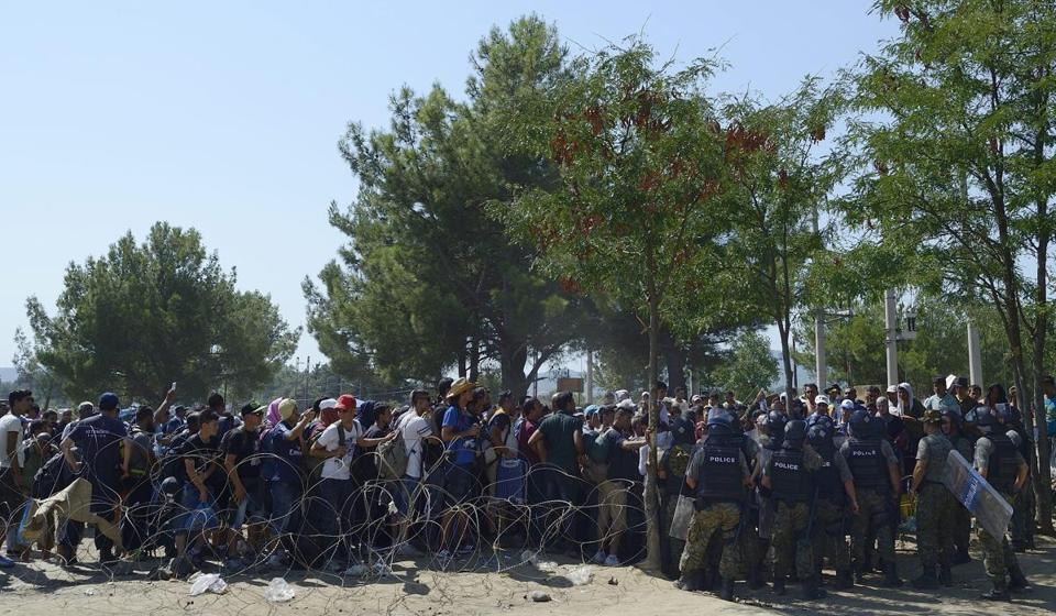 Police officers monitored as a large number of migrants waited to cross the border between Macedonia and Greece near the town of Gevgelija.
