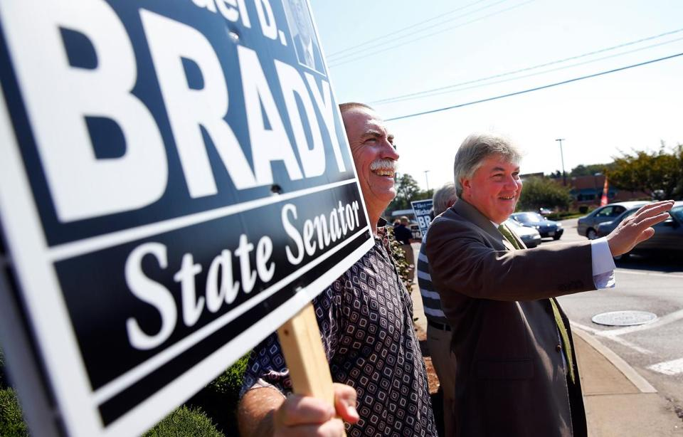 State Representative Michael Brady (right) waved to cars passing by as he campaigned for an open state senate seat.