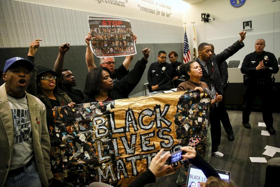 "Demonstrators carried a ""Black Lives Matter"" banner while protesting the death of Ezell Ford during a meeting of the Los Angeles Police Commission in June."