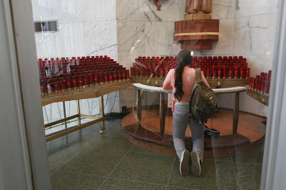 Julie Tamayo, 21, of Brookline prayed at the Shrine of St. Anthony of Padua in Downtown Crossing on Tuesday.