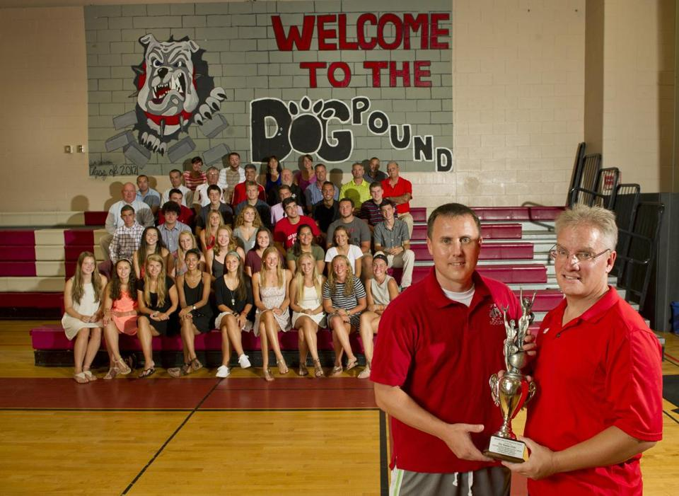 Old Rochester athletic director Bill Tilden (far right) and principal Michael Devoll show off the Dalton Trophy with coaches and athletes in front of the student section, the dog pound, at ORR.