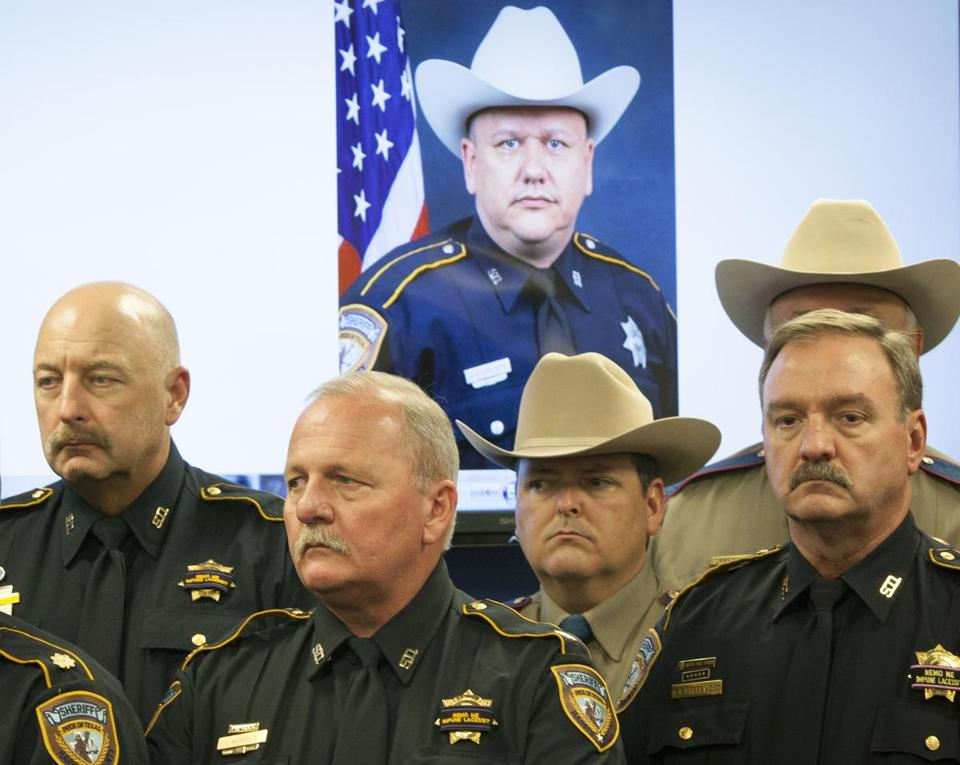 Police officers stood before a portrait of their slain colleague Darren Goforth in Houston on Saturday.