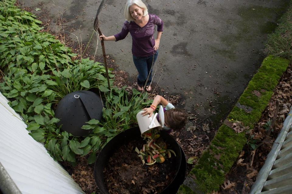 Sarah Birkeland (rear) and her daughter, Abby Edelstein, mixed waste food into their backyard composter.